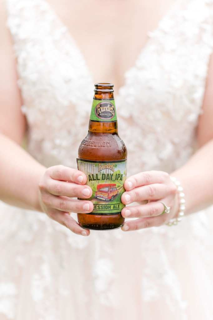 focus on a bottle of beer held by the bride at her waist with both of her hands.