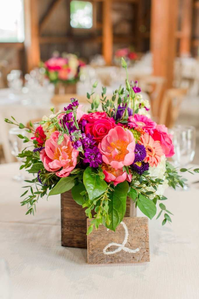 close up of small reception floral arrangement of multicolored wildflowers, roses, peonies in a small wooden box with wooden table numbers