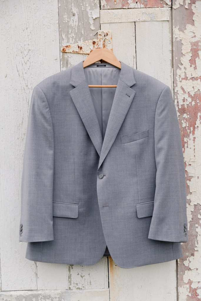 Grey suit jacket hanging on a light brown hanger on the hinge of a weathered white washed barn door