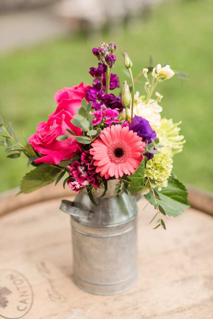 small multicolored wildflower, rose and gerber daisy arrangement in a metal milk jug by the Flower Shop of Pennington Market
