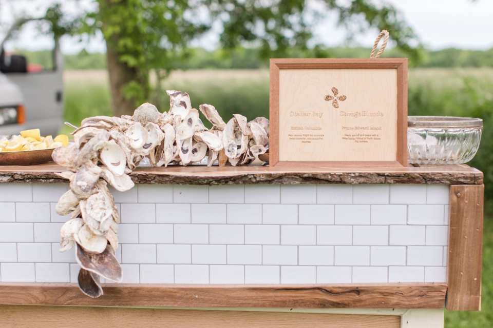 oyster bar set up during cocktail hour with white tiled bar topped with information signage, empty oyster shell garland and lemon wedges on ice by the 13th Street Cocktails Catering