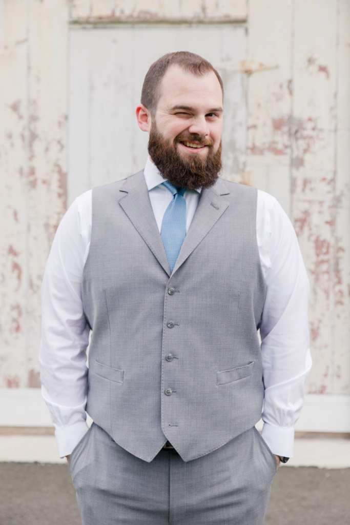 Silly portrait of the groom in his grey vest and blue tie (no jacket), hands in pockets, looking coy at the camera while winking one eye
