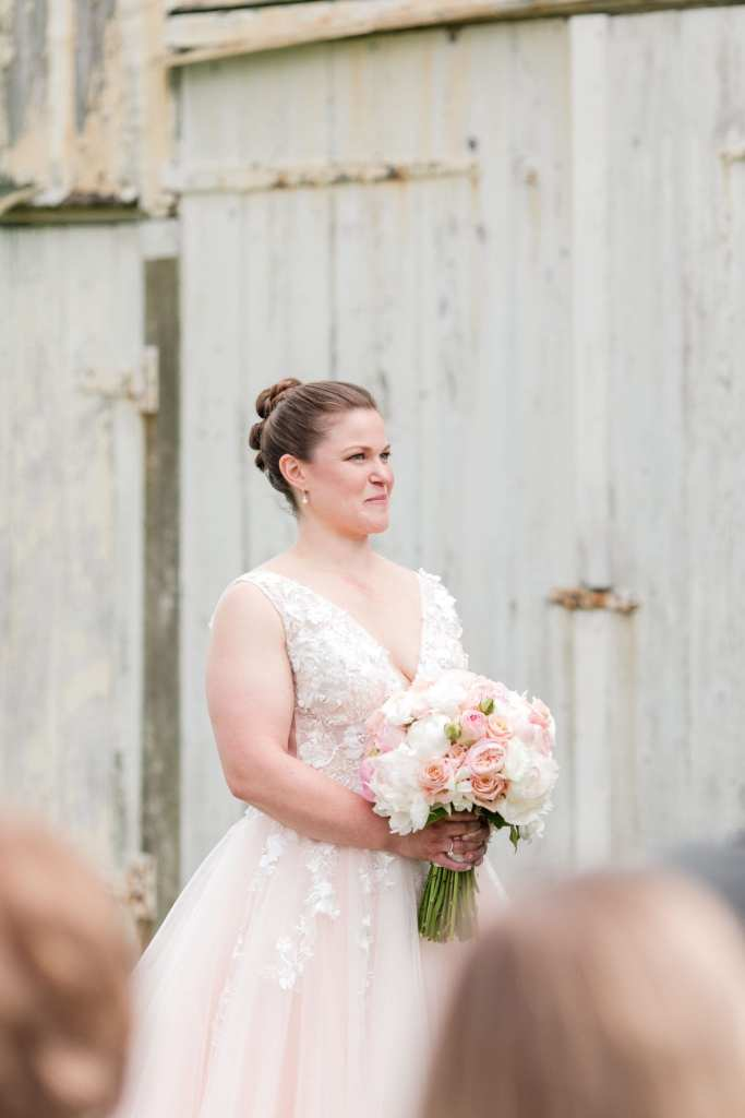 bride grinning in her blush pink v-neck gown with bridal bouquet in her hands at her waist during wedding ceremony