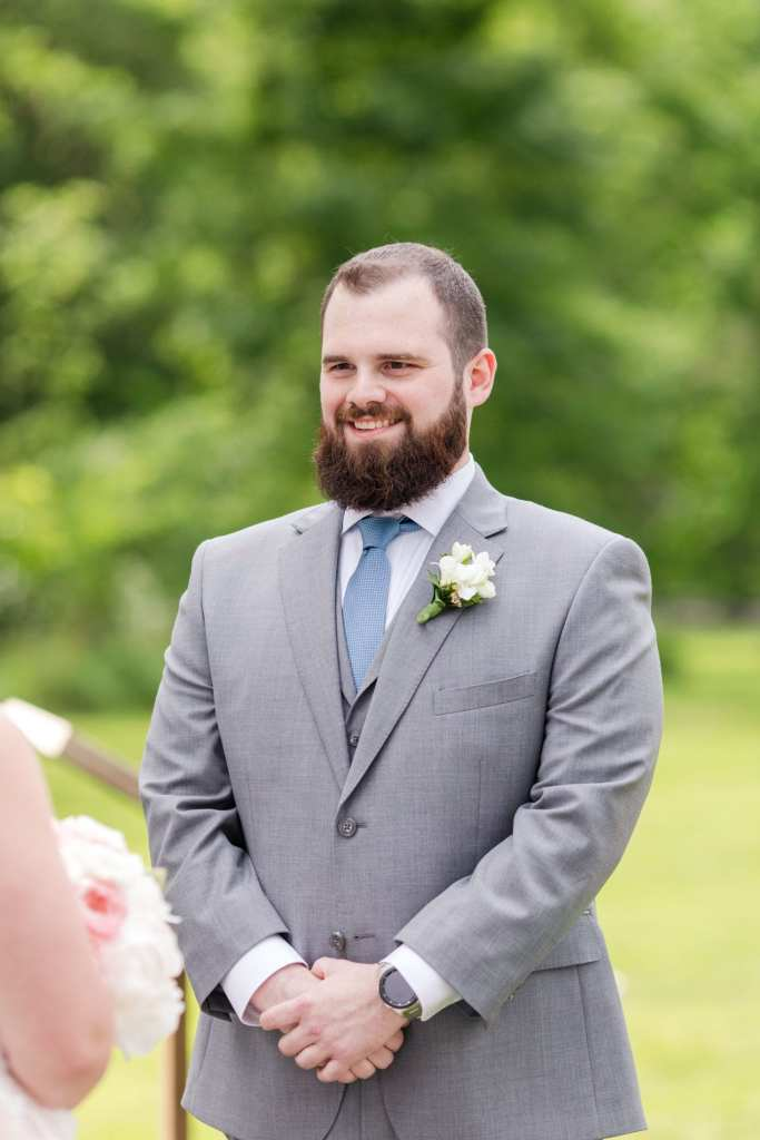 groom smiling while watching his bride walk down the aisle