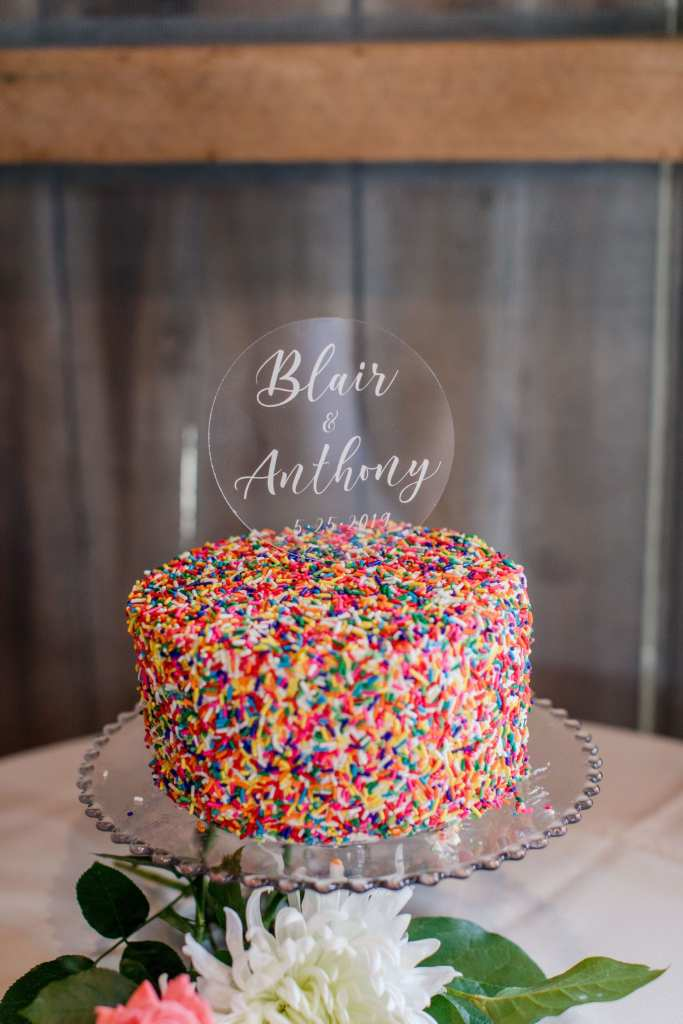 one tier wedding cake covered in rainbow sprinkles on a crystal cake dish with a custom acrylic cake topper with the bride and grooms names and date of wedding