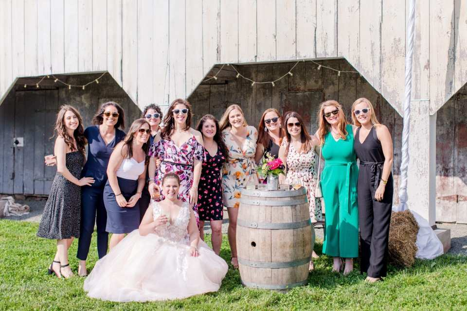 photo of the bride sitting in front of a group of female guests