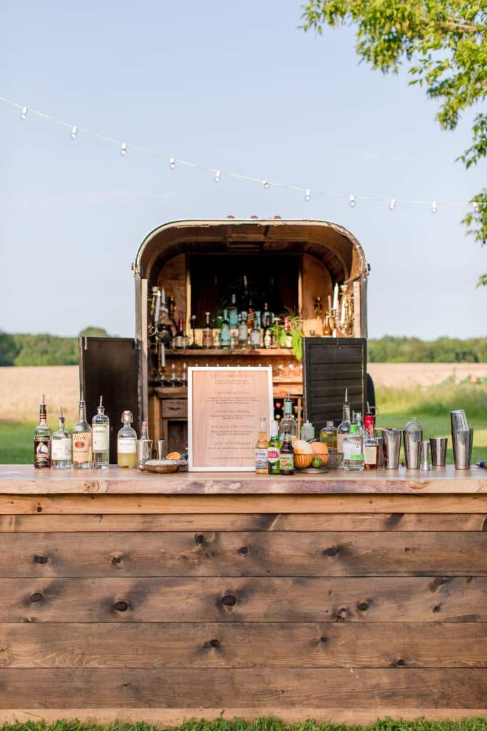 further shot of the horse trailer turned bar behind the wooden bar set up by 13th Street Cocktail Catering