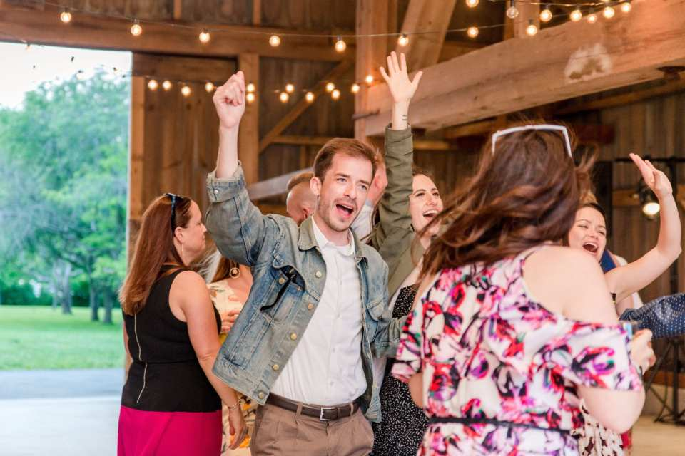 guests dancing during the reception inside the barn