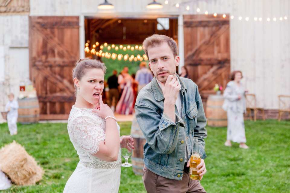 bride in relaxed jumper attire outside of barn posing with a male friend