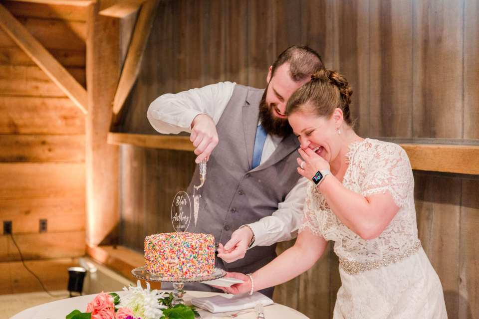 bride and groom laughing while cutting their custom made one tier sprinkle covered wedding cake