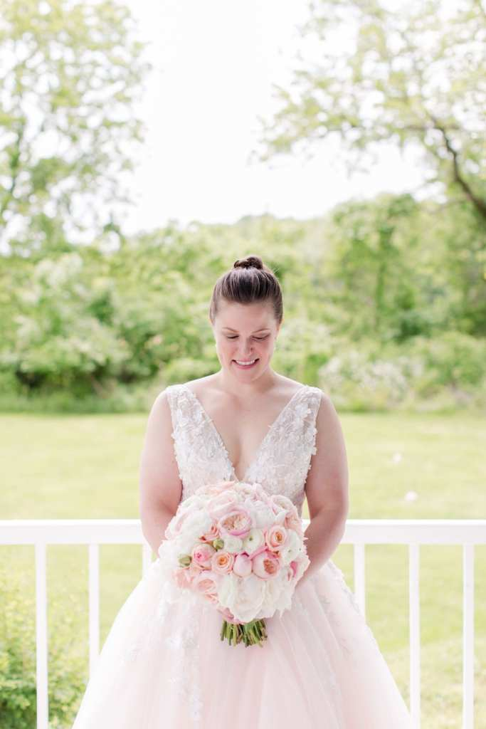 portrait of the bride in a pink v-neck tulle gown by Jovani gazing down at her bridal bouquet of pink and white florals from the Flower Shop of Pennington Market