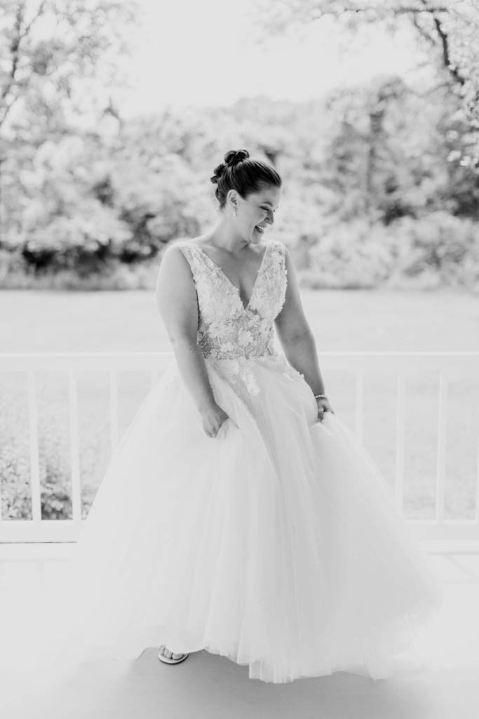 black and white candid photo of the bride holding her tulle gown while dancing on the porch of the farmhouse