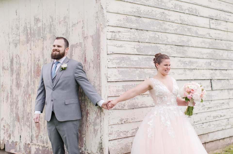 the bride and groom, one on each side of a white washed barn building, holding hands just before the first look