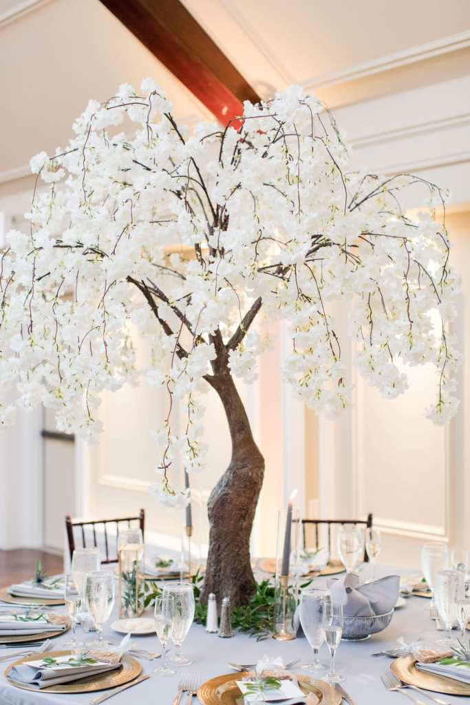 Tall tree centerpieces covered in white draping florals by From Peonies to Paint Chips