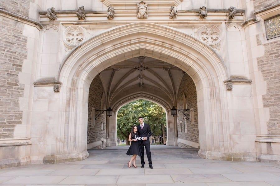 "Bride and groom to be holding a ""love"" sign, while having their arms wrapped around one another's waist, in front of the archway"