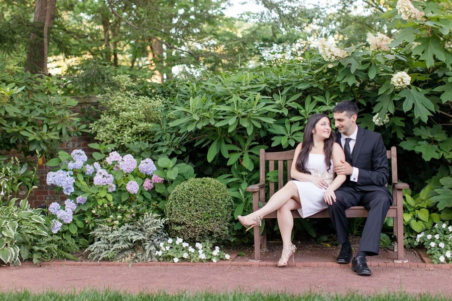 Bride to be in a white strapless short dress with gold applique at the torso by Lilly Pulitzer, gold strappy heels by Badgley Mischka, sitting on a bench with her groom to be (in a black 3 piece suit by Calvin Klein). The bench is in a garden filled with various green foliage, along with a bit of purple hydrangea.