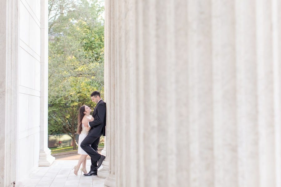 """engaged couple leaning against column of building on the campus of Princeton University. He is in a black suit, leaning against the column, left foot bent up against the colum, she is in his arms, right leg bent up """"hollywood kiss"""" style. She is in a short white strapless dress with gold applique at the waist, along with gold strappy heels, long hair slightly curled and flowing down her back"""