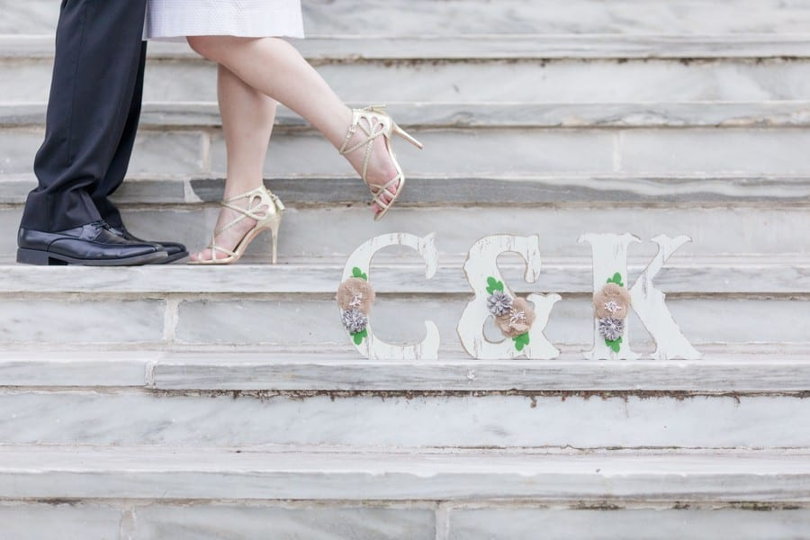 "hand painted, rustic looking ""C & K"" with burlap and small floral decor on them, standing on the marble steps of a building while the couples feet are on the step above. You only see their feet facing each other, with one of her feet in the air ""Hollywood Kiss"" style"