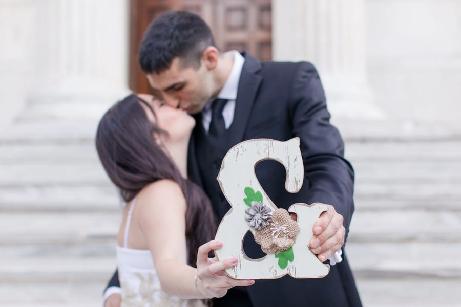 Courtney and Kevin kissing in front of a large building on the Princeton University campus, with two columns, stairs and a set of brown double doors. they are kissing in the distance while holding out a hand painted, rustic looking & in front