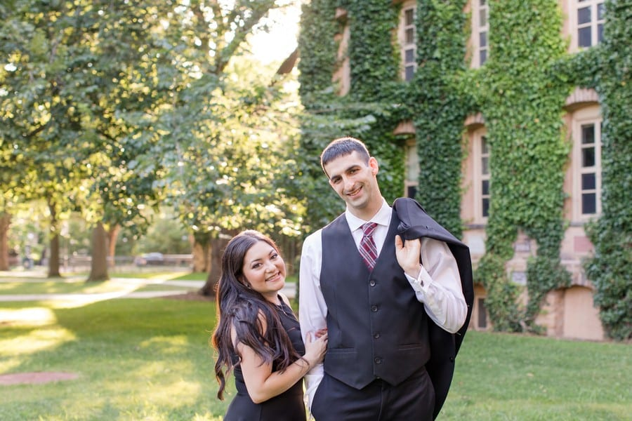 Bride to be in an Aqua black sleeveless short dress with her arms wrapped around the right arm of the groom to be, dressed in a black Calvin Klein 3 piece suit, with his suit jacket thrown casually behind his left shoulder