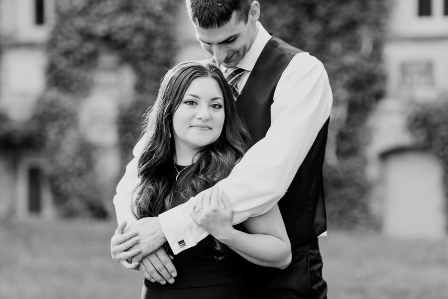 Black and white photo of the bride to be standing in front of her groom to be, wrapped in his arms, she is looking at the camera, he is looking down at her.