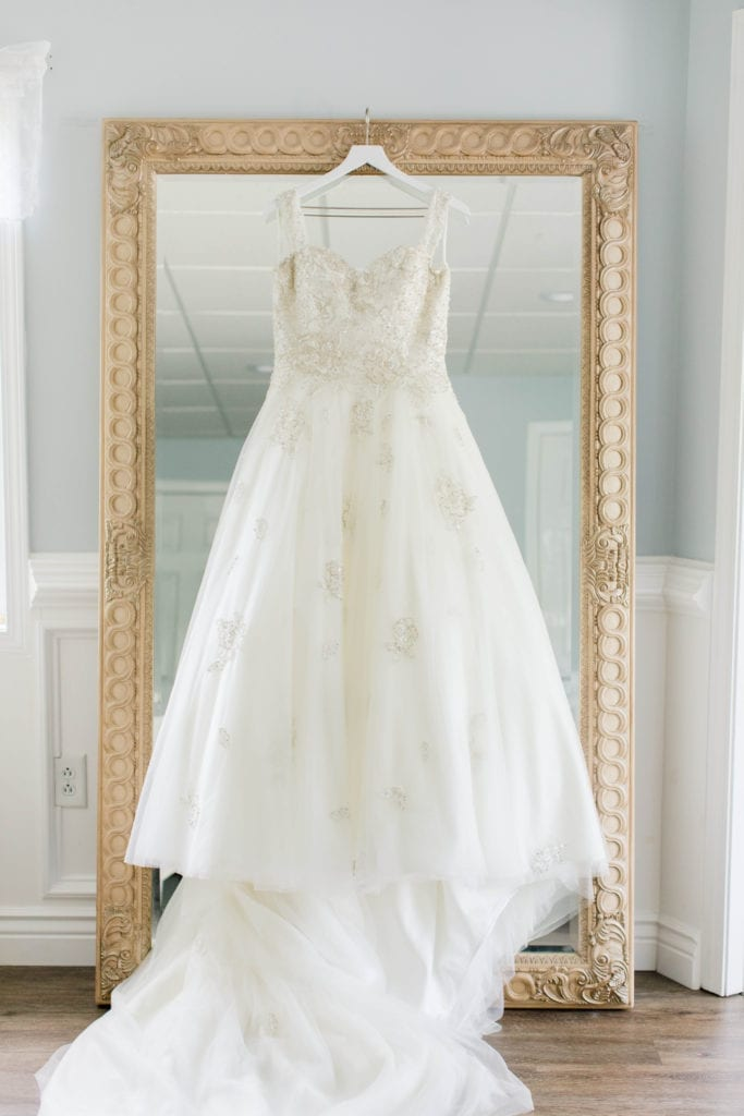 The bridal gown by Justin Alexander hanging on a full length gold framed mirror
