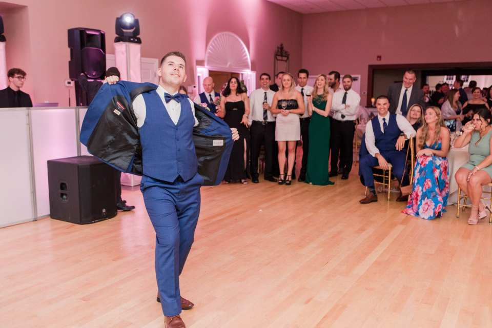 Groom in navy blue tuxedo from the Clothing Center opens his jacket and struts his stuff during the reception