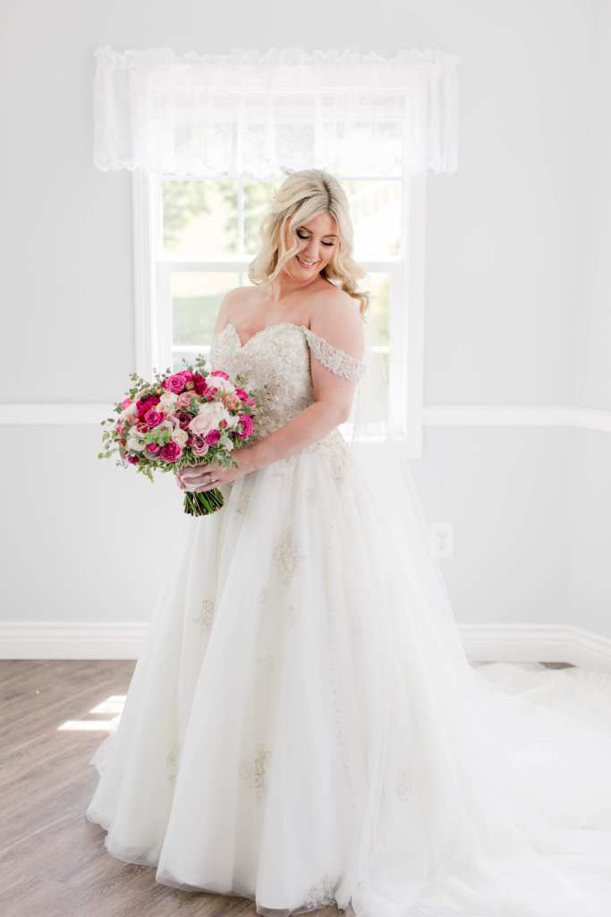 Formal bridal portrait of the bride in her gown by Justin Alexander, bouquet of pinks and white by Pink Dahlia Events