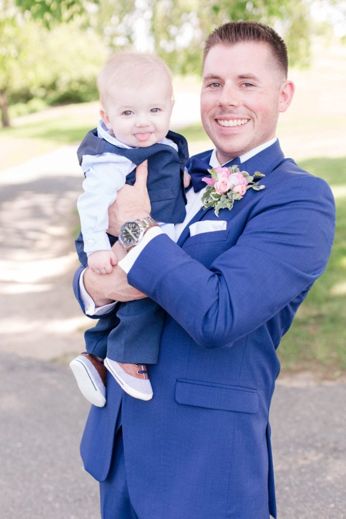 Groom smiling while holding baby boy