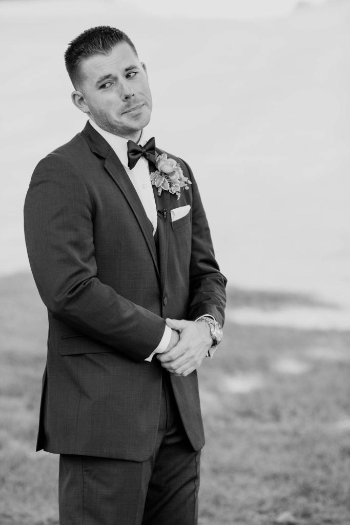 Black and white candid photo of the groom during the first look