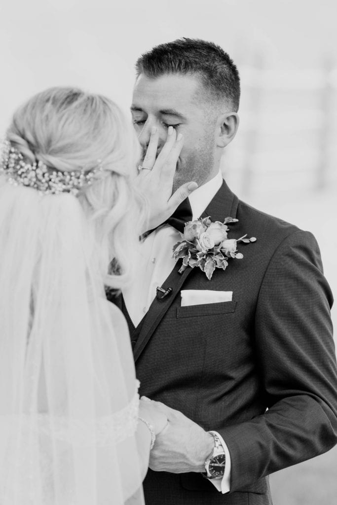 Black and white photo from behind the bride as she wipes away tears on her grooms face during their first look