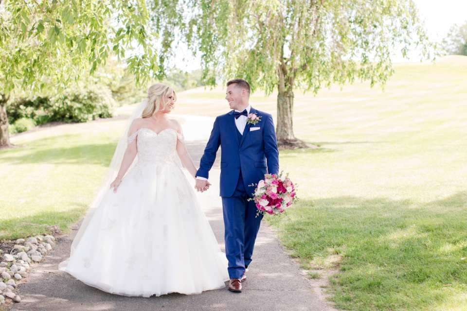 Bride and groom stroll along golf cart path, hand in hand, at the Skyview Golf Club