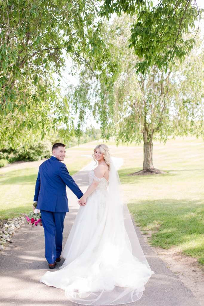 Bride in a Justin Alexander gown holding hands with the groom in a navy blue tuxedo by the Clothing Center, walking away on a golf cart path, from the camera and looking back