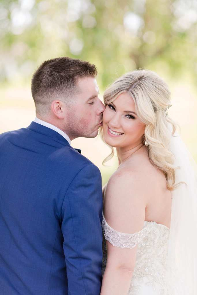 groom kissing the brides cheek as she looks back at the camera, smiling