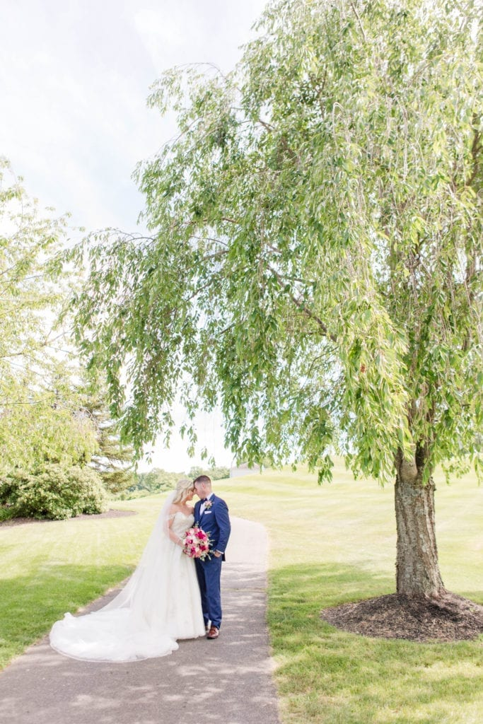 Bride in Justin Alexander gown and groom in navy tuxedo by the Clothing Center on a golf cart path under a large tree, Skyview Golf Club course in background