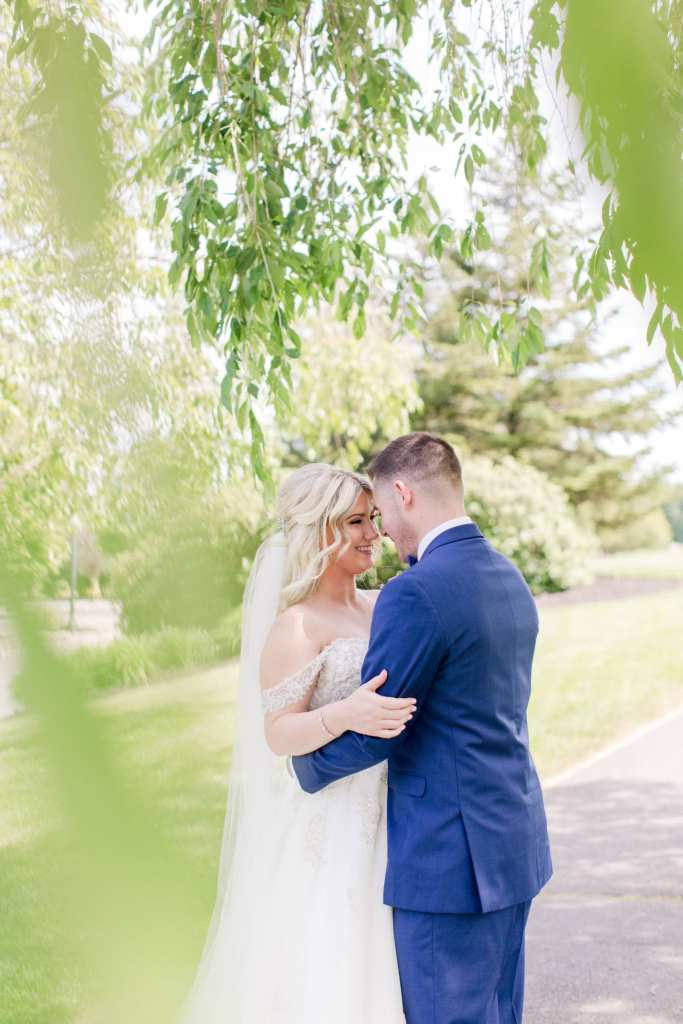 Bride and groom nuzzling amongst the trees at Skyview Golf Club