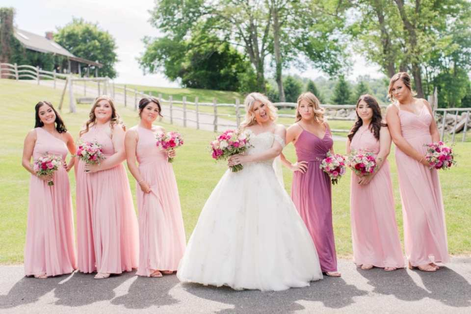 The bride having fun with her bridal party. Brides gown by Justin Alexander, bridal party gowns in shades of pink by David's Bridal. Bouquets by Pink Dahlia Events.