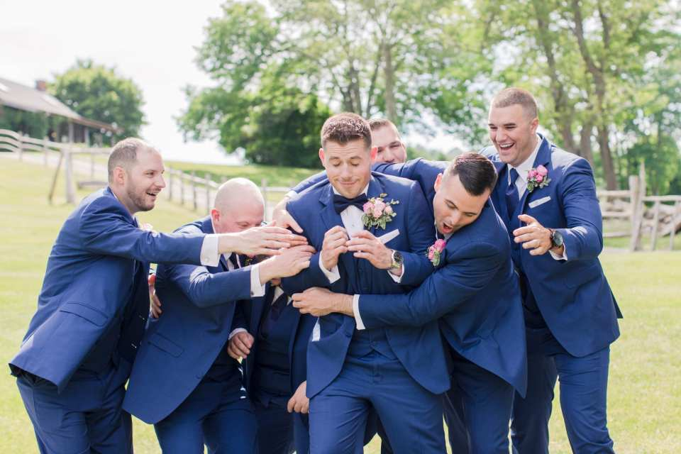 Fun candid photo of the groom being hugged by his groomsmen. Navy blue attire by the Clothing Center