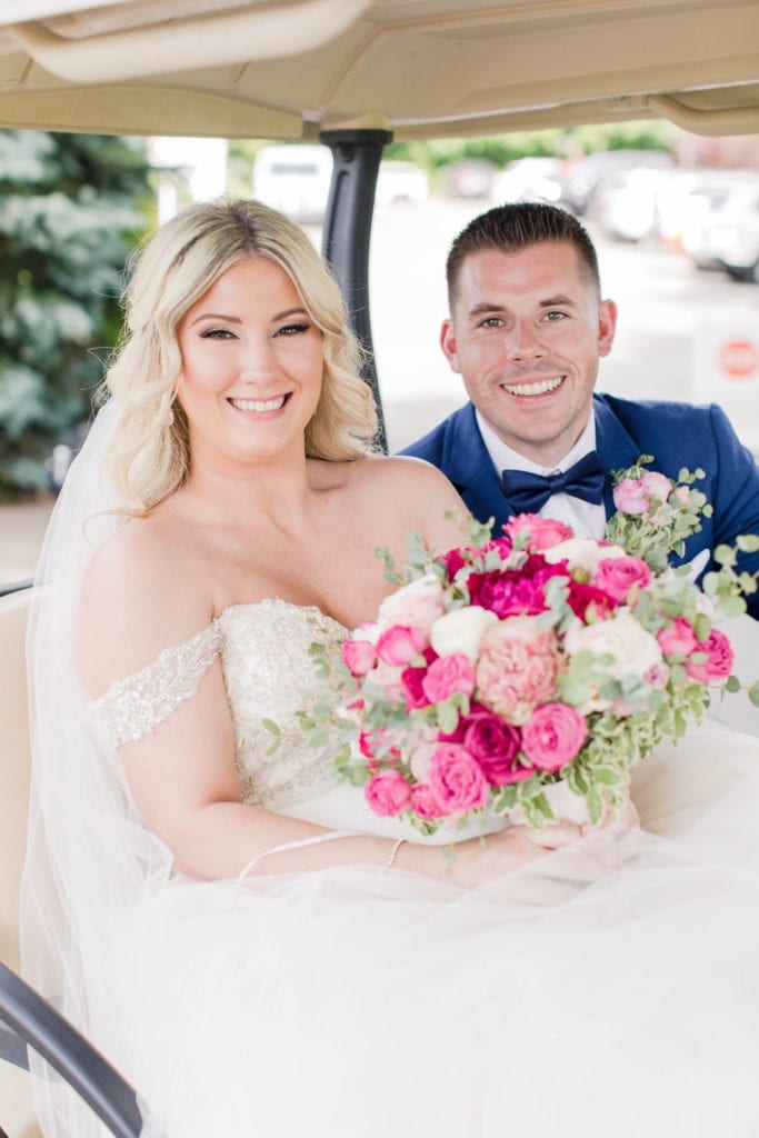 the bride and groom smiling while seated in a golf cart. The brides bouquet of various pink and white florals by Pink Dahlia Events