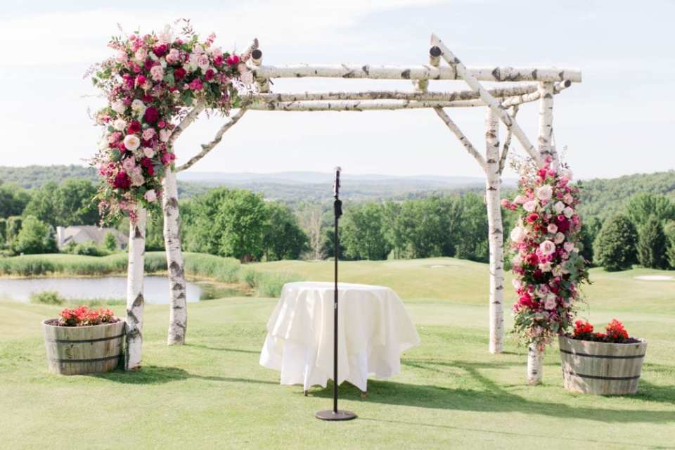 the ceremony area of a four poster birchwood with florals in various shades of pink and white, with greenery, on the top left and bottom right. A small table in the center with white linens and two half barrels on either side of the birchwood with florals in them. The hills covered in green trees in the background. At the Skyview Golf Club.