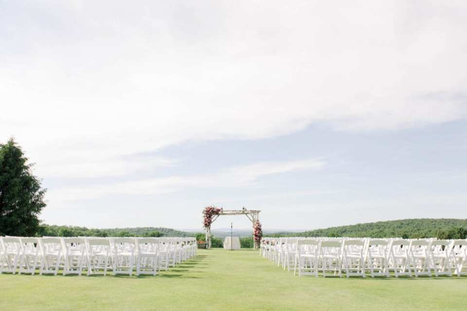 Wide angle shot of the ceremony area. The altar area is made of a four poster birchwood, with florals in various shades of pink and white on the top left and bottom right. The seats on either side of the aisle are white wooden folding chairs. The hills covered in green trees in the background. At the Skyview Golf Club.