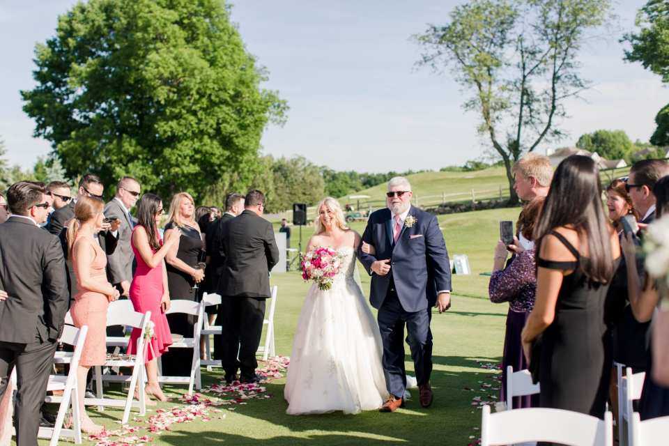 The bride being walked down the aisle by her father. The aisle in lined with rose petals of various pinks and white. She is carrying her bridal bouquet of florals in various shades of pink and white.