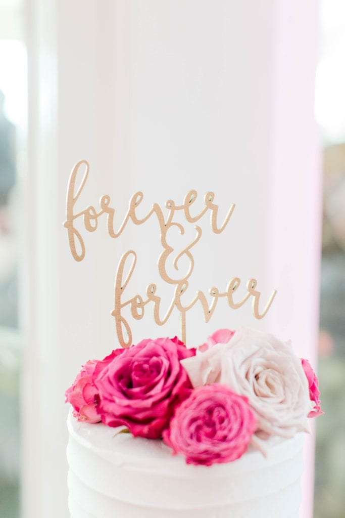 """the gold cake topper saying """"forever & forever"""" atop the white wedding cake with pink and white roses"""