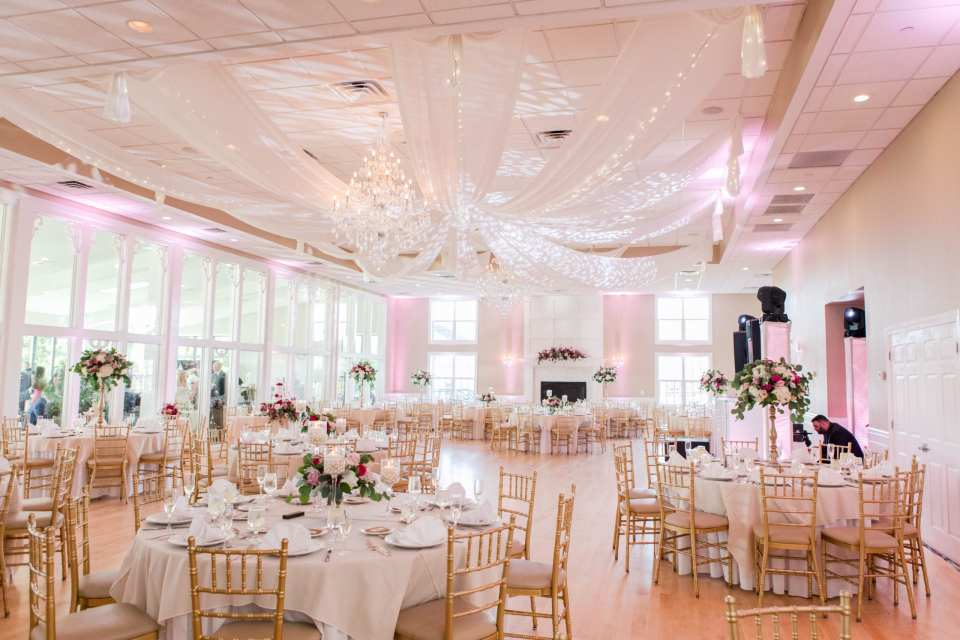 a wide angle photo of the entire ballroom at the Skyview Golf Club with ceiling drapery, crystal chandelier, tables set with white linens, both low and tall floral arrangements and gold chivari chairs