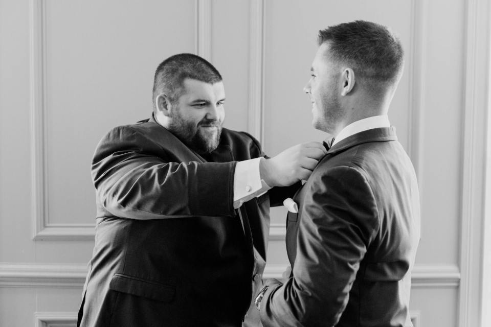 Black and white photo of the grooms bowtie being adjusted by his best man