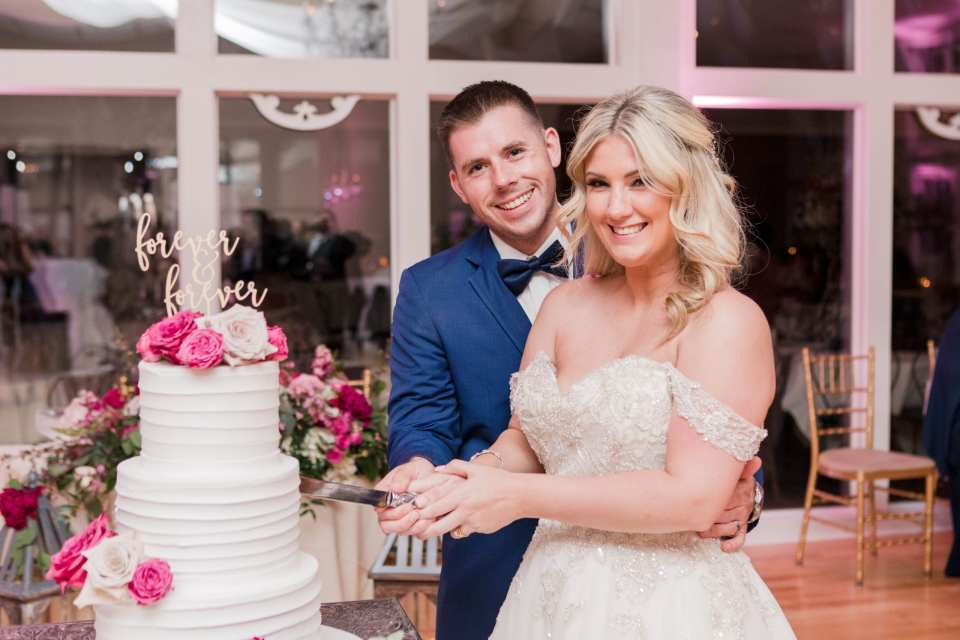 the bride and groom formal portrait during the cake cutting of their multi tiered white cake with pink floral accents by the A Little Cake company