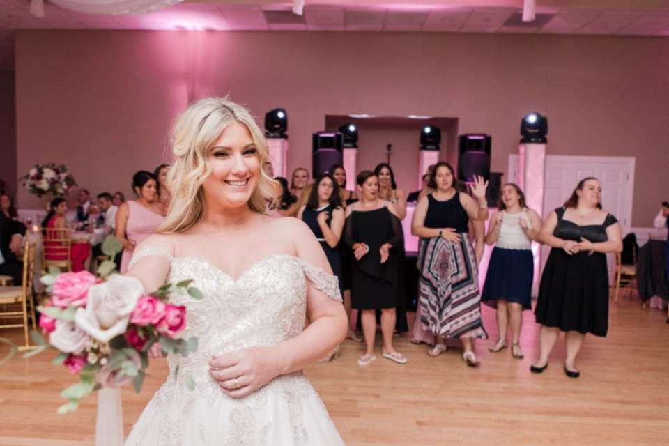 the bride poses with her tossing bouquet, ready to toss it to the female guests waiting behind her