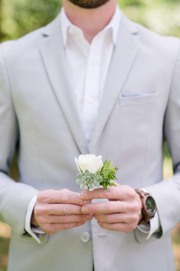 the groom holding his white rose boutenniere