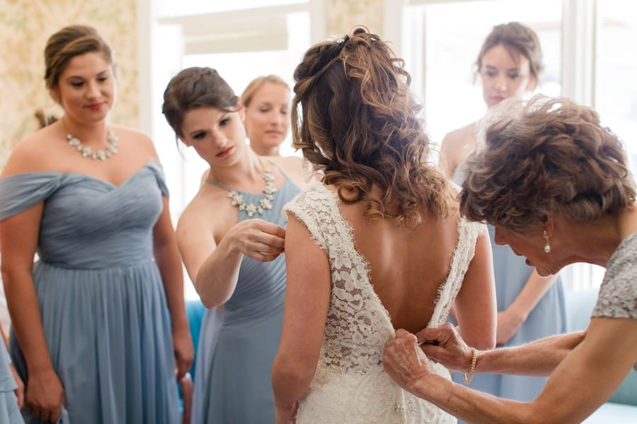 from behind the bride, the mother of the bride buttoning her into her gown, the bridal party in blue gowns look on