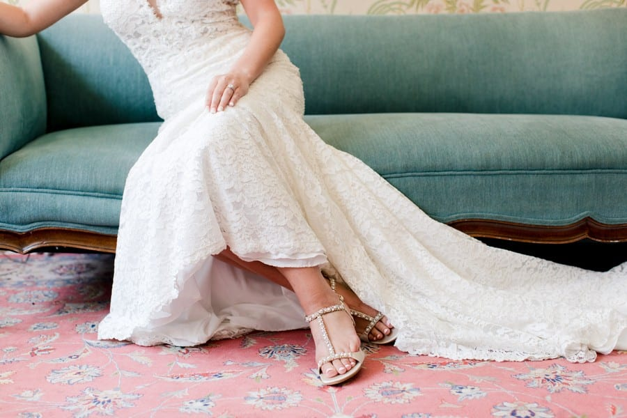 3/4 photo of the bride in her lace Calla Blanche gown on a large green antique couch, Badgley Mischka shoes peeking out